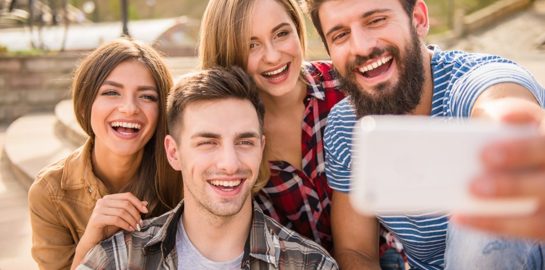 Friends take a selfie on the phone in the street.